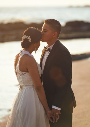 Kissing married wedding couple on sunny beach sunset. Romantic evening for young couple
