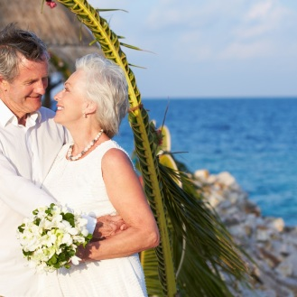 Senior Couple Getting Married In Beach Ceremony Looking At Each Other Smiling